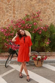 自転車を持つ少女。自転車の花のバスケットとレトロなドレスの女の子。