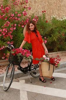 自転車を持つ少女。自転車とバスケットの花を持つ女性。