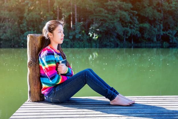 부두에 앉아 책을 가진 어린 소녀.