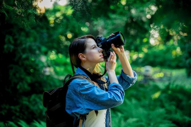 Молодая девушка с фотоаппаратом и рюкзаком в парке