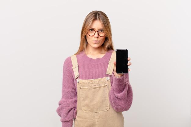 Молодая девушка с камерой грустит, расстроена или злится и смотрит в сторону