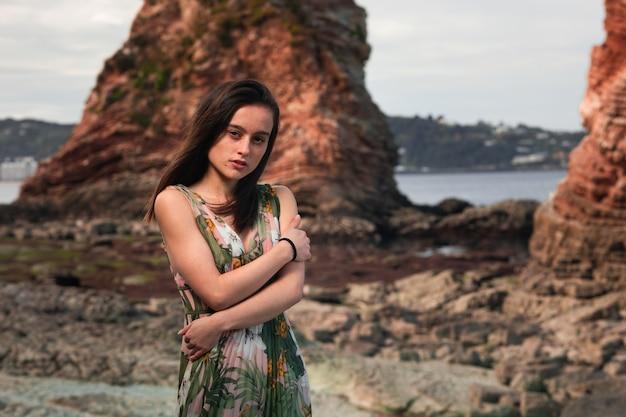 バスク海岸の岩だらけの入り江でポーズをとってカラフルなドレスを着た少女。