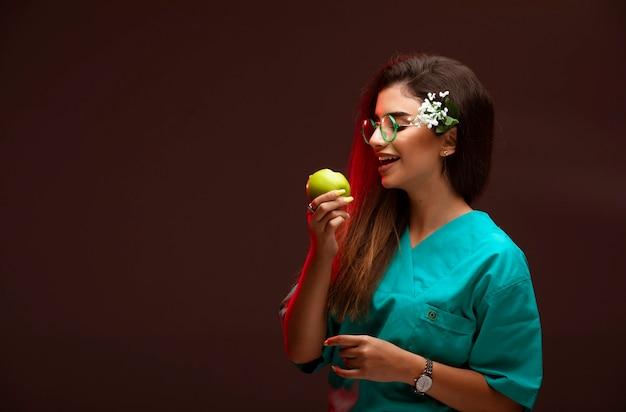 手に青リンゴを持って、かみつく少女。