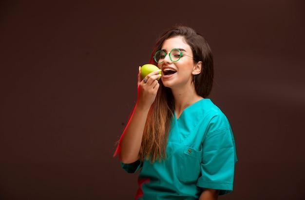 手に青リンゴを食べる少女。