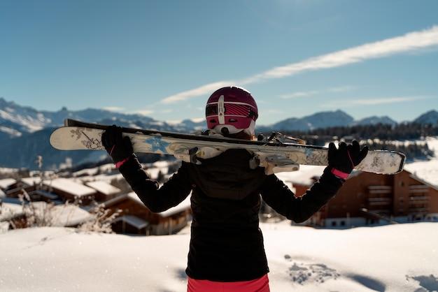 Молодая девушка с парой лыж и лыжным шлемом, глядя на горизонт на горнолыжном курорте в альпах