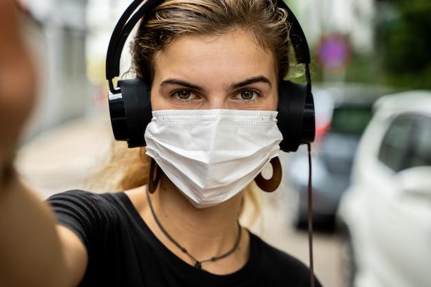防護マスクとヘッドフォンで通りで音楽を聴く若い女の子