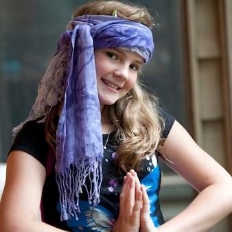 Молодая девушка с шарфом вокруг ее головы создает