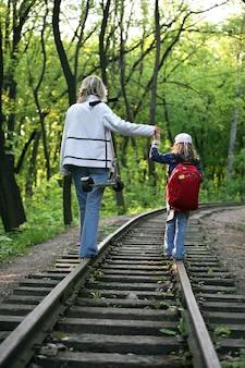 철도 트랙을 걷고 작은 아이와 어린 소녀