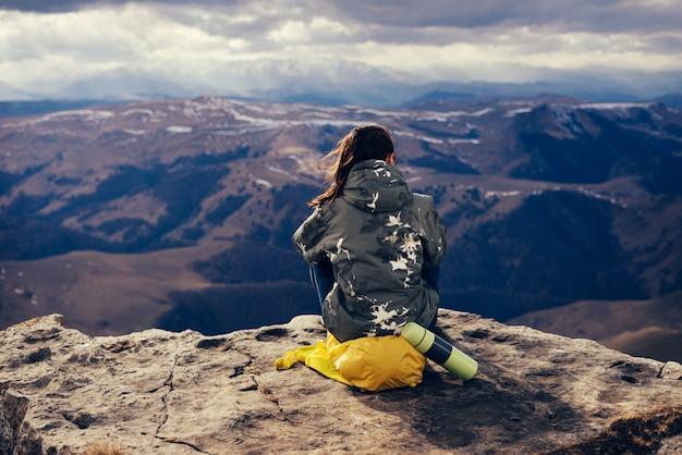 黄色いバックパックを背負った少女が崖の端に座って、山の自然を楽しんでいます