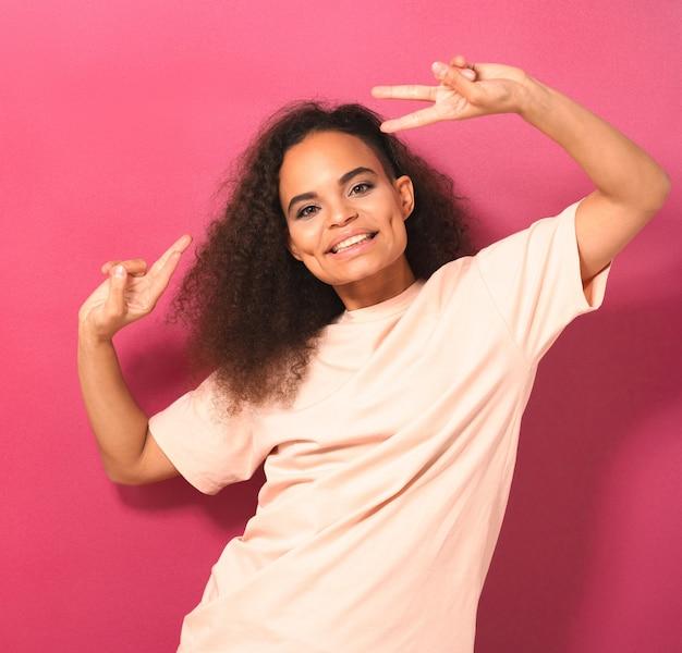 Молодая девушка с афро-волосами, танцующая, жестикулирующая, подняв руки вверх, положительно глядя вперед, в персиковой футболке, изолированной на розовой стене