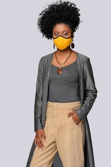 灰色の背中にcovid19分離コロナウイルス保護マスクを身に着けているアフロスタイルの髪の少女