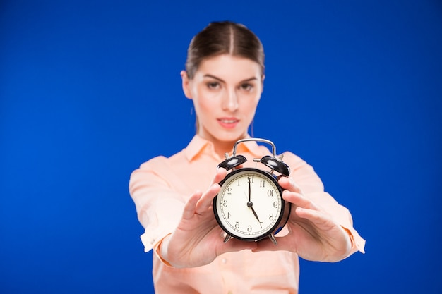 Young girl with an alarm clock in focus