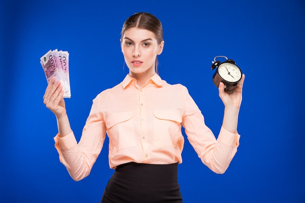 Young girl with an alarm clock and money