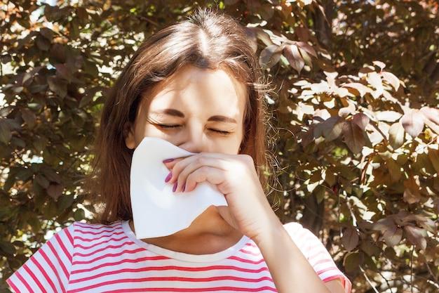 Молодая девушка с аллергией в осеннем парке