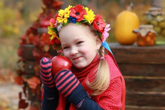 Молодая девушка с яблоком в руке в осеннем парке
