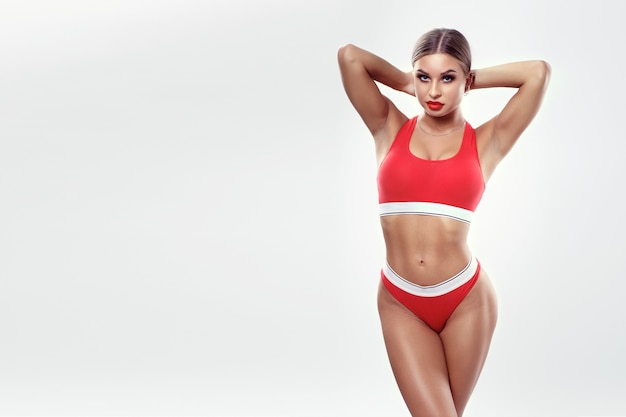 Young girl with an athletic figure in sport underwear on a white background