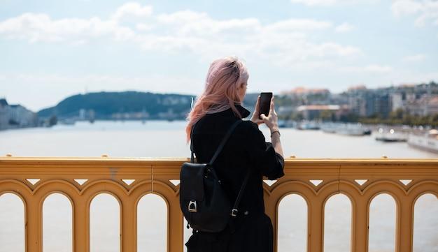 バックパックとピンクの髪の少女、橋からスマートフォンで写真を撮ります。