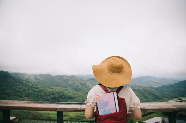 안개 산의 정상에 일몰을 즐기는 배낭 어린 소녀.