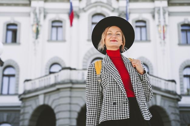 スロベニアに住んでいるリュブリャナ大学ローカルの建物の背景にバックパックを持つ少女