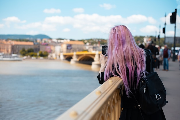 Young girl with backpack and pink hair, take a photo with smartphone from the bridge.