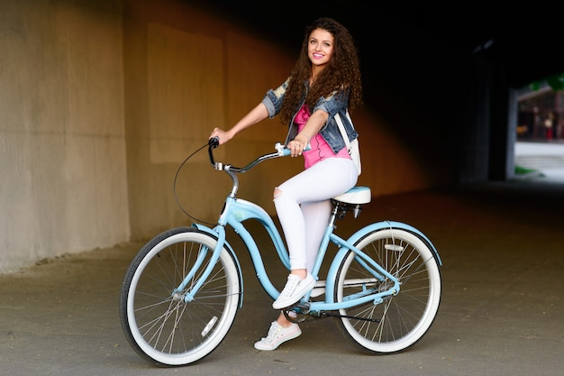 Young girl with beautiful smile and curly hair rides bike in the summer in the city.