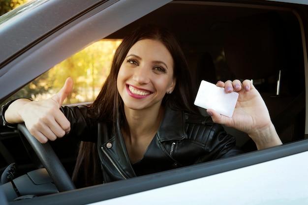 空の白いカードと親指を立てる手のサインを示す白い車に座っている美しい笑顔の少女。女性は運転免許を取得していてとても幸せです。車内のホイールでかわいい女の子が興奮しています。