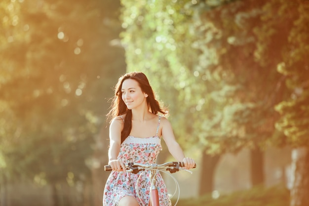 The young girl with bicycle in park