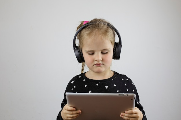 Young girl with big headphones looks into the tablet