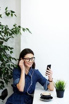 携帯電話と一杯のコーヒー、フリーランスのコンセプト、肖像画、音楽を聴いてカフェに座っている青いストリップシャツと眼鏡を身に着けている黒い髪の少女。