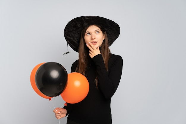 Young girl with black hat and black dress holding ballons