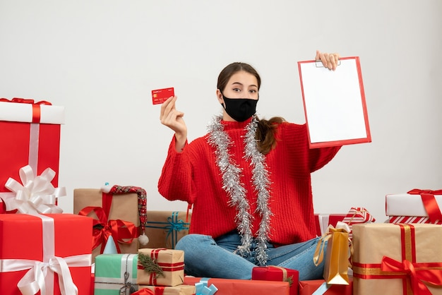 Young girl with black mask holding card and document sitting around presents on white