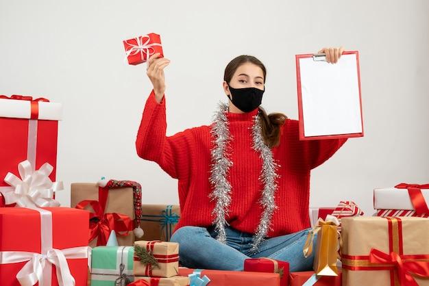 文書を保持し、白い上のプレゼントの周りに座っているプレゼントと黒いマスクを持つ少女
