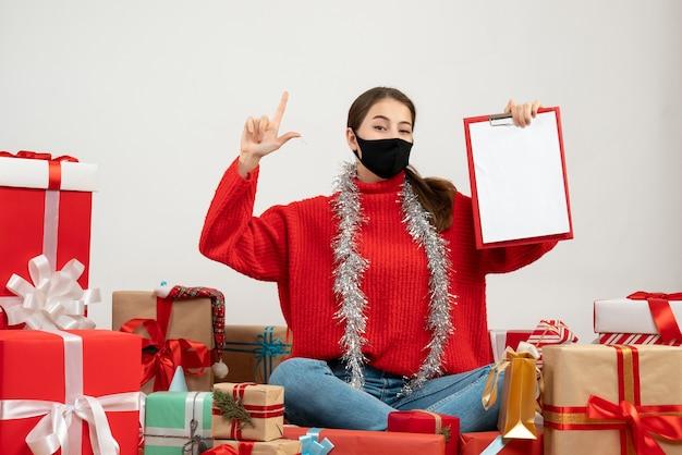 흰색 선물 주위에 앉아 손가락 총을 만드는 문서를 들고 검은 마스크와 어린 소녀