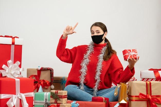 흰색 선물 주위에 앉아 손가락 총 기호를 만드는 선물을 들고 검은 마스크와 어린 소녀