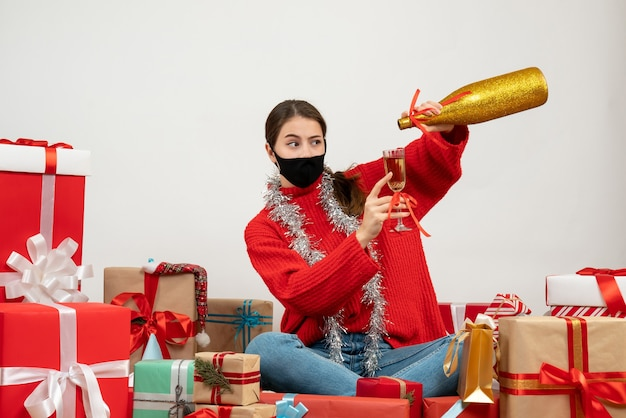 Young girl with black mask pouring champagne sitting around presents on white