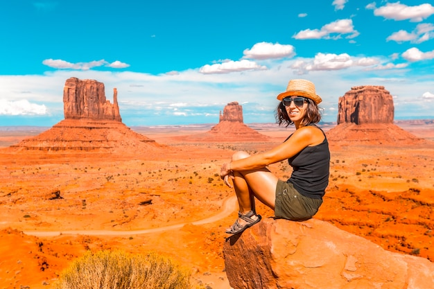 A young girl with black t-shirt sitting in the center of the photo on a stone in the monument valley national park