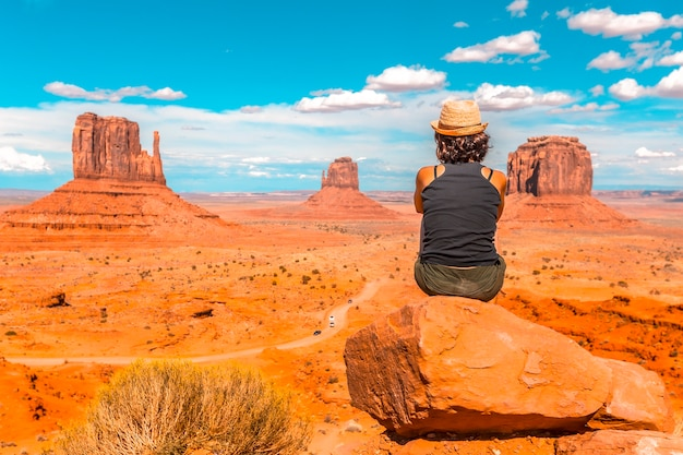 A young girl with black t-shirt sitting to the right of the photo on a stone in the monument valley