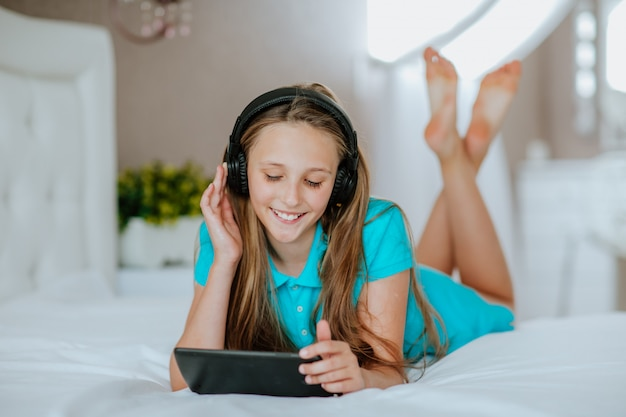 Young girl with black tablet in white bedroom