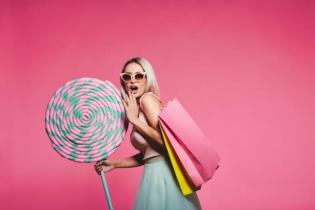 거대한 달콤한 막대 사탕으로 서있는 상단과 치마를 입고 금발 머리를 가진 어린 소녀