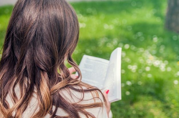녹색 정원에서 책을 가진 어린 소녀입니다. 무료 행복한 여자. 아는 것이 힘이다. 지식에 대한 갈증. 여자 손에 예약