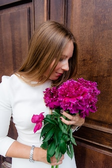 Young girl with a bouquet of bright peonies on a walk around the city
