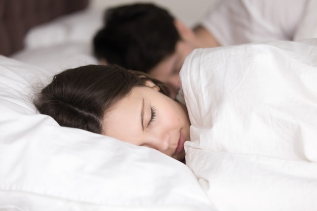 Young girl with boyfriend sleeping peacefully in cozy white bed