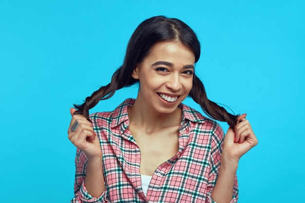 Young girl with bright smile playing with her ponytails against blue wall