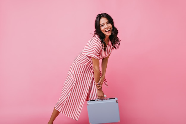 Young girl with brown eyes poses with suitcase. brunette in striped midi dress laughs.