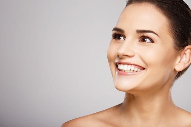 Молодая девушка с каштановыми волосами, чистой свежей кожей и обнаженными плечами позирует на сером студийном фоне, модель с легким обнаженным макияжем, идеальными зубами, сияющей улыбкой.