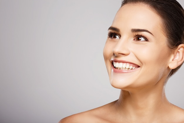 Young girl with brown hair, clean fresh skin and naked shoulders posing at gray studio background, a model with light nude make-up, perfect teeth, shining smile.