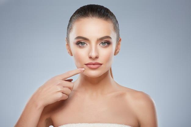 Молодая девушка с каштановыми волосами, зафиксированными сзади, чистой свежей кожей, большими глазами и обнаженными плечами, позирует на сером студийном фоне и смотрит в камеру, указывая на губы.