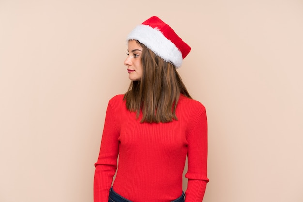 Young girl with christmas hat over isolated background looking side