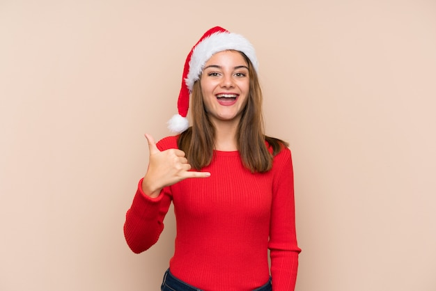 Young girl with christmas hat over isolated wall making phone gesture