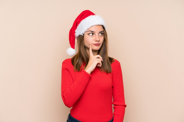 Young girl with christmas hat over isolated wall thinking an idea